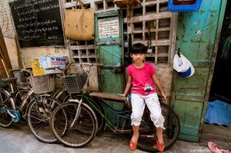 Cô bé này đang ngồi trước căn nhà của mình trong một con hẻm chỉ đủ rộng cho đúng một chiếc xe máy đi vào, 2016
