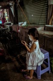 Em bé ngồi chơi một mình khi mẹ dọn hàng lúc tám giờ tối, chợ Căn Cứ, Gò Vấp, 2018